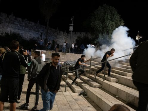 Palestinians react to stun grenades fired by Israeli police to clear the Damascus Gate to the Old City of Jerusalem after clashes at the Al-Aqsa mosque compound (Maya Alleruzzo/AP)