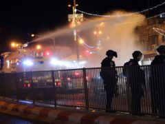 Israeli police use a water cannon to disperse Palestinian protesters near the Damascus Gate to the Old City of Jerusalem (AP)