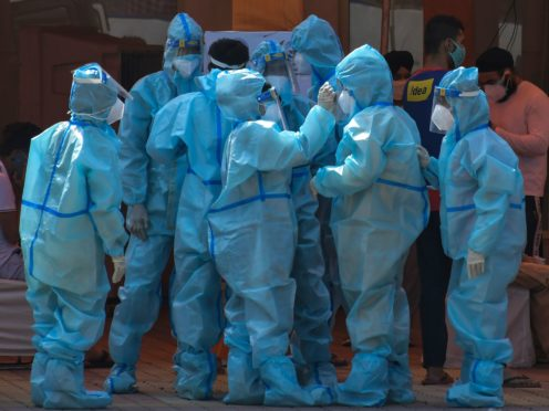 Health workers and volunteers in personal protective suits wait to receive patients outside a Covid-19 hospital that was set up at a Sikh Gurdwara in New Delhi, India (Ishant Chauhan/AP)