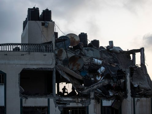 A Palestinian searches for survivors under the rubble of a destroyed roof of a residential building in Gaza City which was hit by Israeli missile strike (Khalil Hamra/AP)