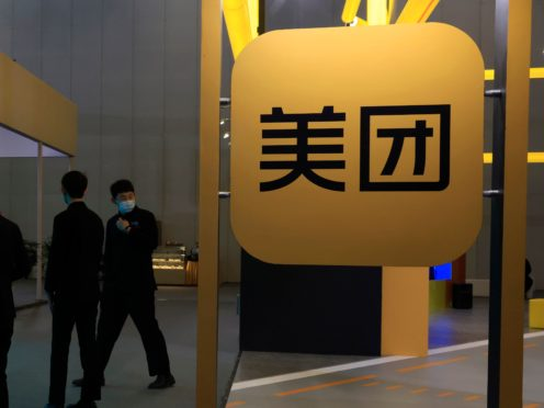 Workers walk past the logo of Meituan in Beijing (Ng Han Guan/AP)