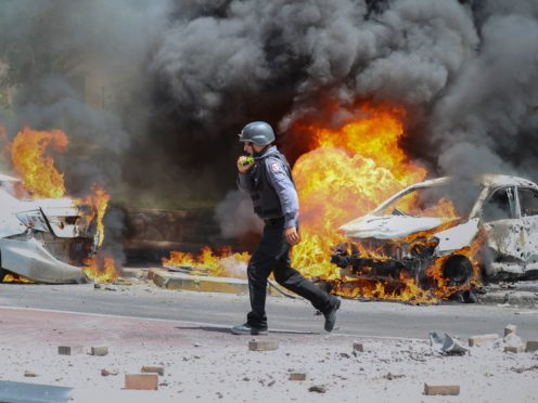 An Israeli firefighter walks next to cars hit by a missile fired from the Gaza Strip in the southern Israeli city of Ashkelon (Ariel Schalit/AP)
