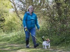 An actress playing the role of PCSO Julia James walks her Jack Russell dog, Toby, in the area where she was found dead as part of a police reconstruction (Kirsty O'Connor/PA)