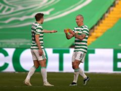 Scott Brown passes the armband to James Forrest after being substituted during his final home match (Andrew Milligan/PA)