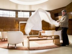 Paul Fretwell removes dust sheets from the furniture in the Grand Entrance at Eltham Palace in London (Ian West/PA)