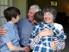 Sue and Alan Rickett hug their grandchildren Ben (left) and Isaac (right) for the first time in over a year (Martin Rickett/PA)