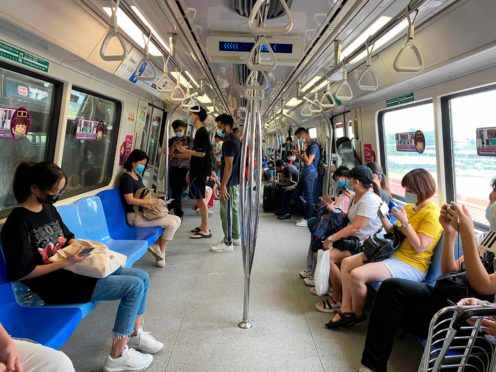 Commuters wear face masks and practise social distancing while onboard an underground train in Singapore (Zen Soo/AP)