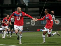 Burak Yilmaz celebrates with Renato Sanches after scoring a penalty which helped Lille clinch the Ligue 1 title (Lewis Joly/AP/PA)