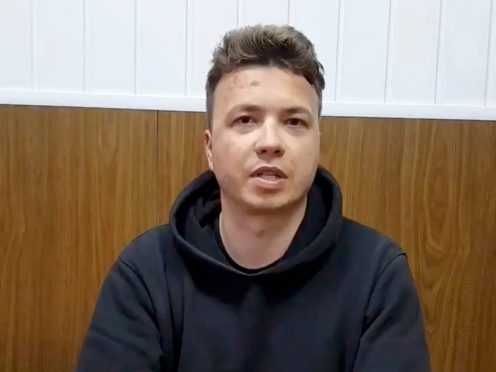 """Roman Protasevich speaks to a camera in a prison in Minsk, Belarus. The brief video clip of Pratasevich in custody was shown on Belarusian state television Monday night. He sat at a table with his hands folded in front of him and spoke rapidly, saying he was in satisfactory health, and that his treatment was """"maximally correct and according to law."""" He added that he was giving evidence to investigators about organizing mass disturbances. (Belarus Government press office via AP)"""