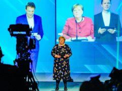 Norway's prime minister, Erna Solberg, on stage, with online screen image of German chancellor Angela Merkel, behind, as Nordlink is turned on (Gorm Kallestad/NTB via AP)