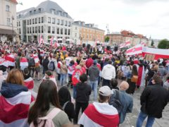 Protesters wear traditional Belarusian flags at a demo in Poland (AP)