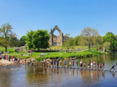 Tackling the stepping stones at Bolton Abbey in North Yorkshire (PA)