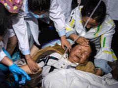 Medical workers treat a woman after an earthquake in Yangbi Yi (Xinhua/AP)