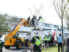 Emergency services use a cherry picker to attempt to remove protesters and dismantle the bamboo lock-ons they are using to block the road outside the Newsprinters printing works at Broxbourne, Hertfordshire (PA)