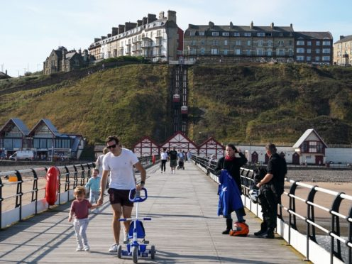 People on the pier at Saltburn-by-the-Sea, North Yorkshire, which has been identified by Halifax as one of England's least expensive market towns to buy a home (Owen Humphreys/PA)