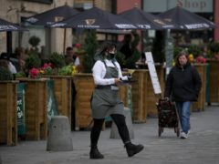 A server carries a tray of drinks from a pub in the Grassmarket in Edinburgh (Andrew Milligan/PA)
