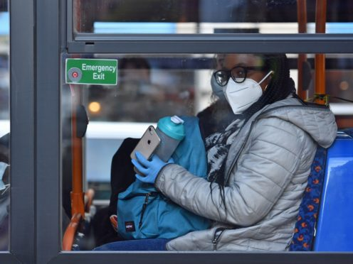 Less restrictive measures such as wearing face coverings on public transport may remain in place (Jacob King/PA)