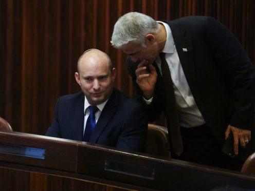 Naftali Bennett, left, speaks to Yair Lapid (Ronen Zvulun/Pool Photo via AP)
