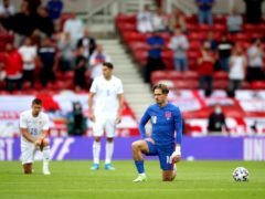 England's Jack Grealish (right) takes a knee as Romania's Ionut Nedelcearu (back) stands, ahead of the international friendly match at the Riverside Stadium (Nick Potts/PA)