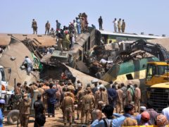 Soldiers and volunteers work at the site of a train collision in the Ghotki district in southern Pakistan (Waleed Saddique/AP)