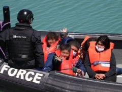 A group of people, including children, thought to be migrants are brought in to Dover (Gareth Fuller/PA)