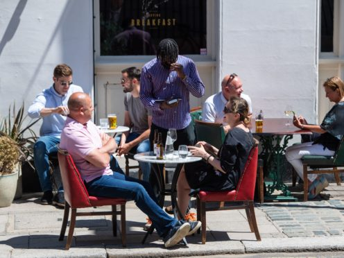 People eat and drink at tables outside a pub in central London (Dominic Lipinski/PA)