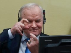 Former Bosnian Serb military chief Ratko Mladic imitates taking pictures as he sits the court room in The Hague (Peter Dejong/AP)