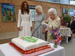 The Duchesses of Cambridge and Cornwall watch as the Queen cuts the cake with a sword (Oli Scarff/PA)
