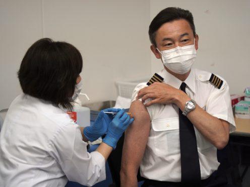 All Nippon Airlines pilot Satoru Shimizu receives a Covid-19 vaccination at Haneda Airport (Kantaro Komiya/AP)