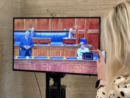 A woman watches a television screen showing DUP leader Edwin Poots (left) in the Stormont Assembly at Parliament Buildings in Belfast pays tribute to Arlene Foster (Liam McBurney/PA)