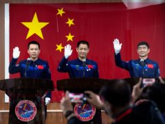 Chinese astronauts (from left) Tang Hongbo, Nie Haisheng, and Liu Boming wave at a press conference ahead of the launch (Ng Han Guan/AP)