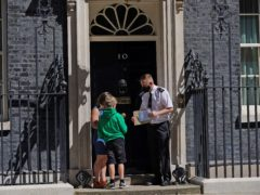 Ilmarie Braun with her son, nine year-old Thomas Braun, whose brother Eddie has severe, complex epilepsy, stands outside Number 10 Downing Street in London with a copy of his personal letter to the Prime Minister urging him to help get an NHS prescription for medical cannabis (Yui Mok/PA)