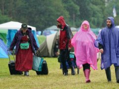 People cover up from the rain on the first day of Download Festival at Donington Park in Leicestershire (Joe Giddens/PA)