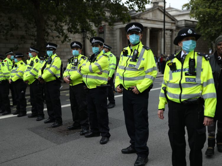 Police officers wearing face masks (PA)