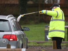 A test and trace worker in the Bramley Inn car park near Basingstoke in Hampshire, takes a coronavirus test from a driver (Andrew Matthews/PA)