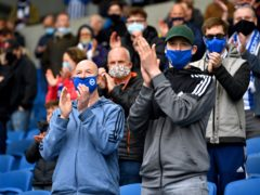Fans in masks applaud their team (PA)
