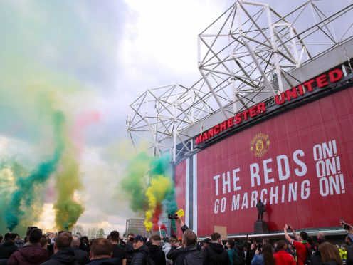 Fans let off flares as they protest against the Glazer family (Barrington Coombs/PA)