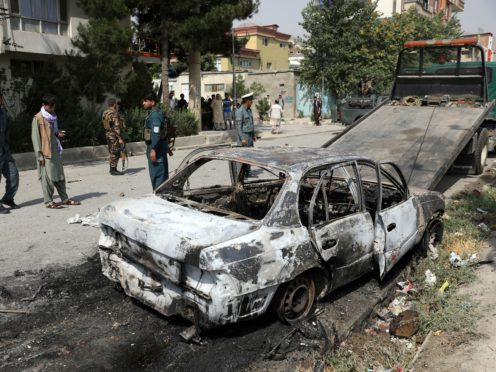 Security personnel inspect a damaged vehicle where rockets were fired from in Kabul, Afghanistan (Rahmat Gul/AP)