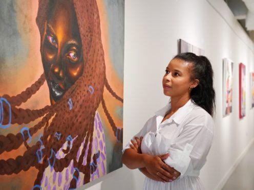 A Hofa Gallery employee looks at 'Serena' by Chinaza Agbor (Jonathan Brady/PA)