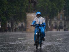 A man rides a bike along Whitehall as heavy rain sweeps through central London (Victoria Jones/PA)