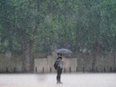 A woman stands in the rain in Horse Guards Parade, Westminster as heavy rain sweeps through central London. Thunderstorms bringing lightning and torrential rain to the south are set to continue until Monday, forecasters have said (PA)