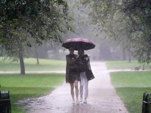 Two women walks through heavy rain in St James's Park in central London (Victoria Jones/PA)