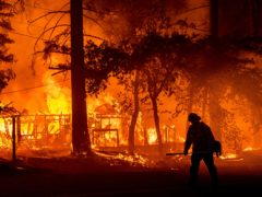 A firefighter passes a burning home as the Dixie Fire flares in Plumas County (AP)