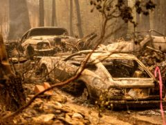 Following the Dixie Fire, scorched vehicles rest in a driveway in the Indian Falls community of Plumas County, Calif., on Monday, July 26, 2021. (AP Photo/Noah Berger)