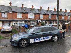Police at the scene in Brompton Park, Belfast, where a baby died and another young child was critically injured (PA)