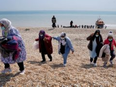 Migrants make their way up a beach after crossing to the UK via boat (Gareth Fuller/PA)