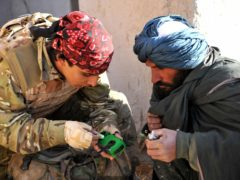Ministry of Defence undated handout photo of an interpreter working for ISAF, gives a local man a wind up radio, supplied by ISAF as he takes part in Operation Zamary Kargha. An air insertion operation has been mounted by British soldiers and Afghan police, re-establishing government control in an area of Helmand province previously under heavy Taliban influence.