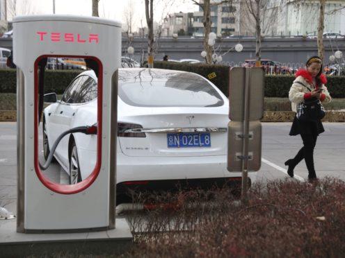 A woman walks past a Tesla car being charged in Beijing (Ng Han Guan/AP)