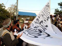 Taliban fighters pray while raising their flag at the Ghazni provincial governor's house (Gulabuddin Amiri/AP)