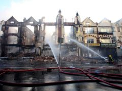 Fire crews douse burnt-out buildings in Croydon during riots in 2011 (Gareth Fuller/PA)